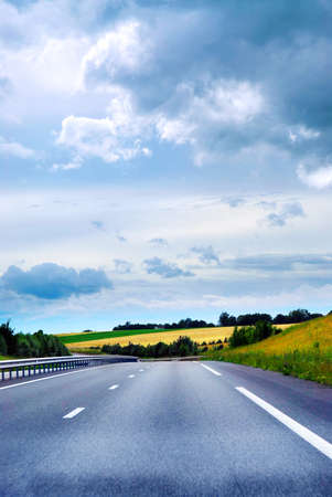 Empty road among fields with blue cloudy sky Stock Photo - 1482572