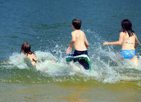 Group of young children running into water at the beach