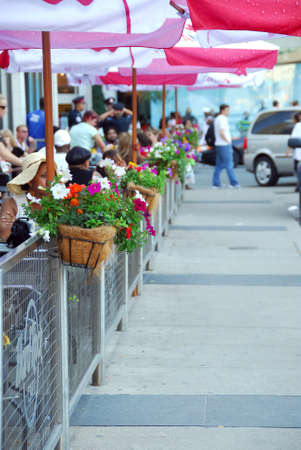 사람들로 가득 찬 꽃으로 장식 된 울타리 뒤의 보도 카페 스톡 콘텐츠