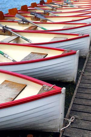 docked: Fila de botes a remo de madera acoplado en alquiler