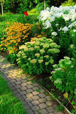 Garten mit gepflasterten Pfad und blühende Blumen im Spätsommer