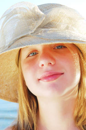 Portrait of a teenage girl wearing a straw hat on a beach photo