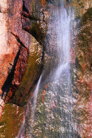 Water flowing down over big granite rock photo