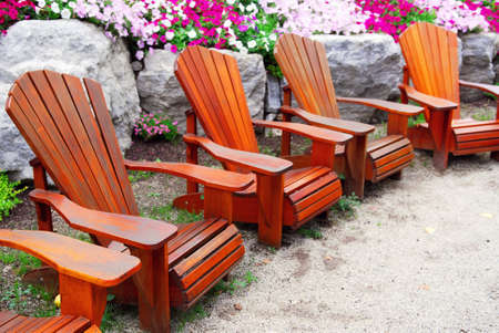 Row of solid wood patio chairs and natural stone landscaping Stock Photo