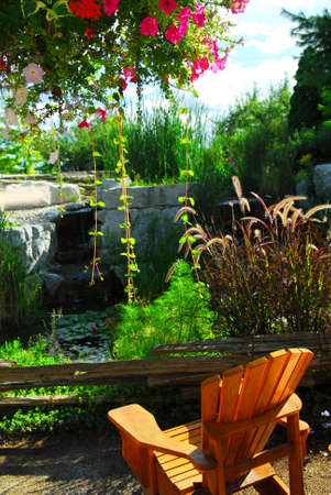 Natural stone pond and patio landscaping with wooden chair  photo
