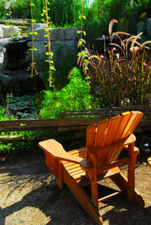 Natural stone pond and patio landscaping with wooden chair Stock Photo - 1620944