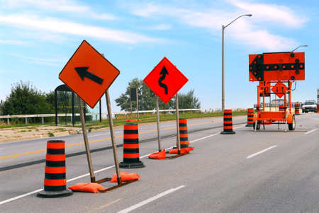 road block: Road construction signs and cones on a city street