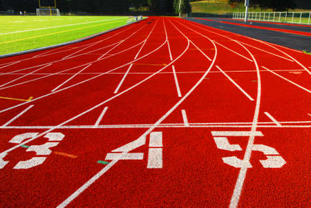 Lanes of a red race track with numbers and green football field Stock Photo - 1638068