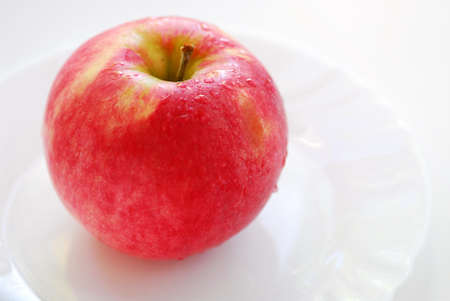Red dewy apple on a white plate Stock Photo - 1685524