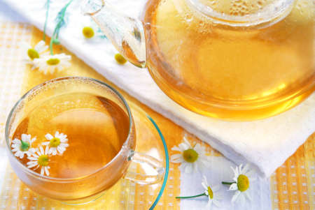 chamomile flower: Teacup and teapot with soothing chamomile tea Stock Photo