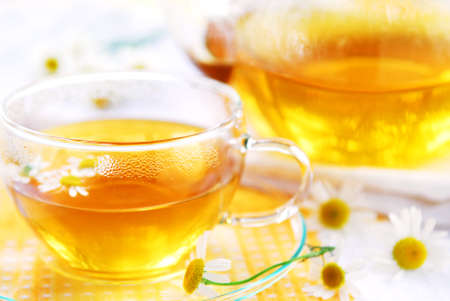 A teacup and a teapot with herbal camomile tea photo