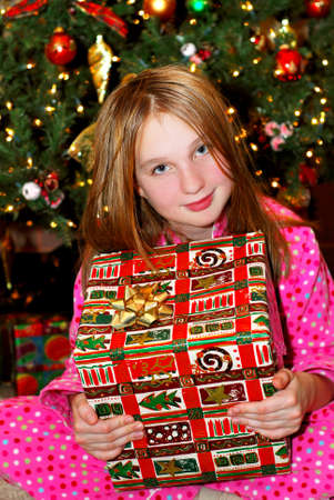 Young girl holding a big Christmas present sitting under a Christmas tree photo
