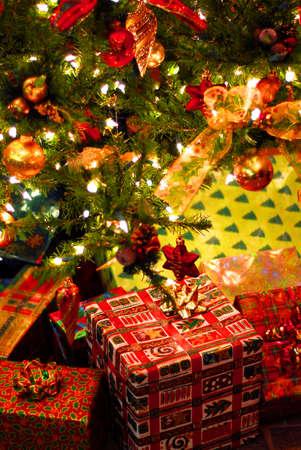 dar un regalo: Regalos envueltos bajo un �rbol de Navidad decorado Foto de archivo
