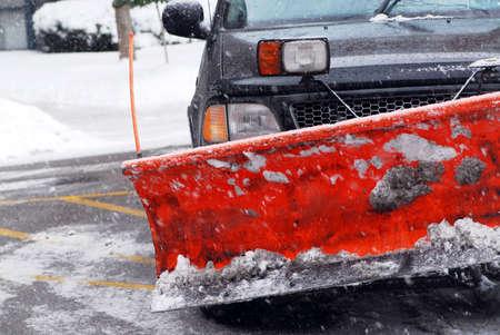 ploegen: Sneeuw ploeg vrachtwagen op een weg tijdens een sneeuwstorm