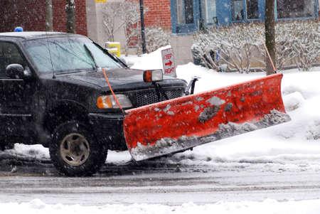 ploegen: Sneeuw beploegen vrachtwagen op een weg tijdens een sneeuwstorm Stockfoto