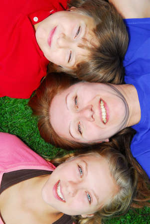 Portrait of a family - mother and children - lying on grass in a park photo