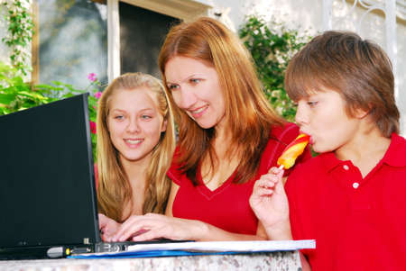 are working: Mature woman working on computer at home with her children