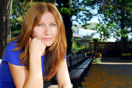 thinking woman: Mature woman looking sad and tired sitting on a park bench