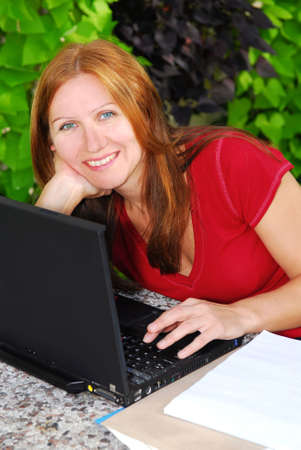 Happy mature woman working on portable computer at home, small business owner photo