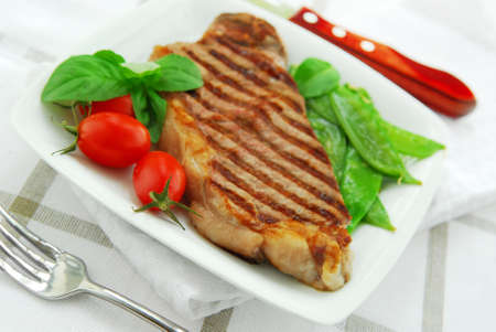 Grilled New York beef steak served on a plate with vegetables Stock Photo