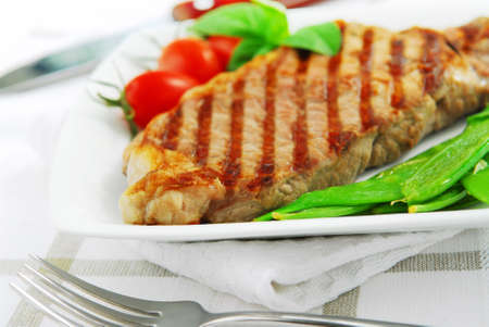 Grilled New York beef steak served on a plate with vegetables Stok Fotoğraf