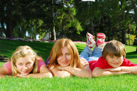 Family of happy mother and children relaxing on green grass photo