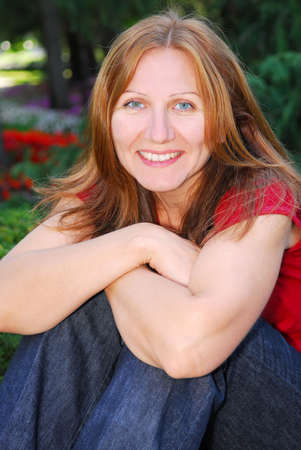 Portrait of smiling attractive mature woman relaxing in summer park Stock Photo