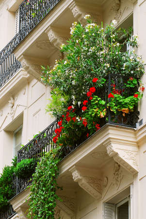 balcony: Wrought iron balcony full of flowers on historic building in Paris, France