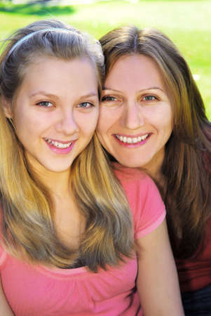 mid teens: Portrait of a smiling mother and teenage daughter in summer park Stock Photo