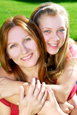 Portrait of a smiling mother and teenage daughter in summer park photo