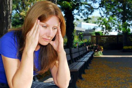 cansancio: Pareja mujer con un dolor de cabeza sentado en el banco de parque