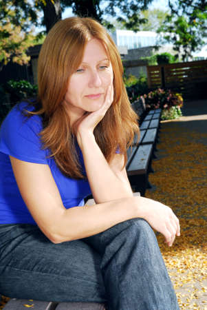 성숙한 여자 슬픈 찾고 스트레스 공원 벤치에 앉아 스톡 콘텐츠