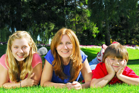 Portrait of a mother with her children lying on the grass in a park photo