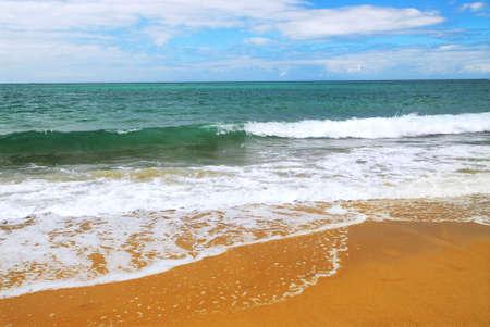 advancing: Ocean wave advancing on a yellow sandy beach