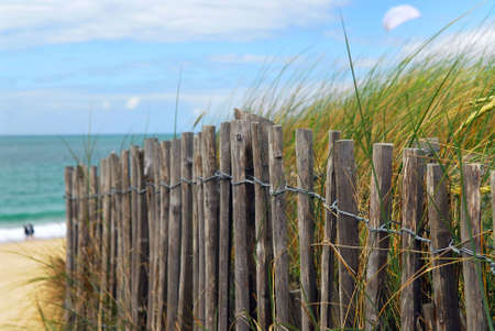 clear path: Old wooden fence on a beach in Brittany, France Stock Photo