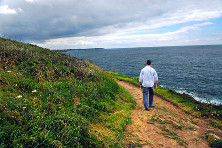 A man walking on a hiking trail along the coast of Brittany, France photo