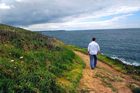 Un hombre caminando sobre un sendero a lo largo de la costa de Bretaña, Francia