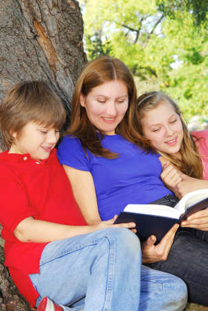 under a tree: Family of mother and children reading a book under a tree in summer park