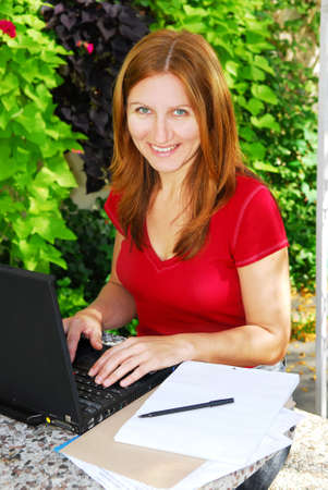 Happy mature woman working on a portable computer in her garden photo
