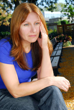 Mature woman looking sad and stressed sitting on a park bench Stock Photo - 1979926