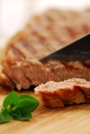 Grilled steak being cut on a cutting board, closeup photo