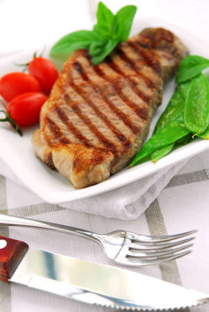 Grilled New York steak served on a plate with vegetables photo