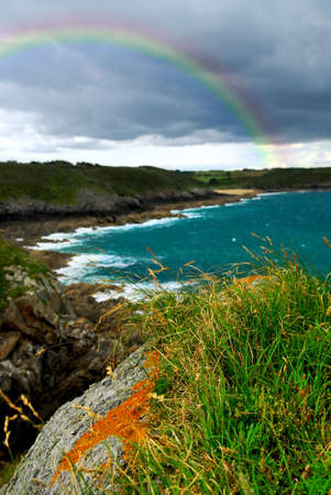 Landscape of rocky Atlantic coast in Brittany France with stormy sky and rainbow