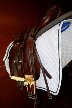 girth: Saddle on a rack in a tack room, horseback riding equipment Stock Photo