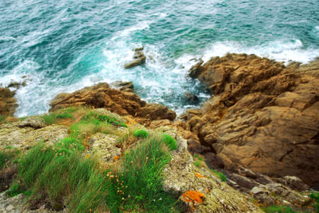 View down the cliffs at Atlantic ocean coast in Brittany, France photo
