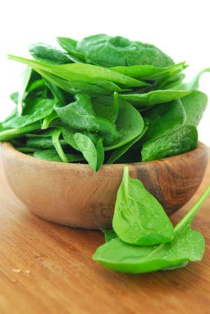 espinacas: Espinacas frescas IIN un cuenco de madera en una tabla para cortar