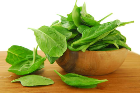 Fresh spinach iin a wooden bowl on a cutting board photo