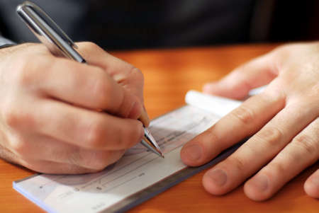 checkbook: Closeup sobre el hombre `s manos escribir un cheque  Foto de archivo