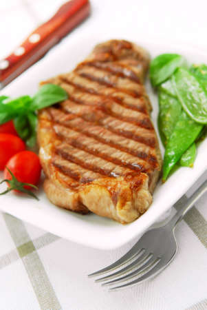 served: Grilled New York beef steak served on a plate with vegetables Stock Photo