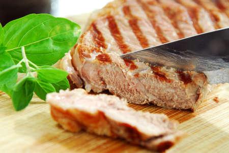 Grilled steak being cut on a cutting board, closeup